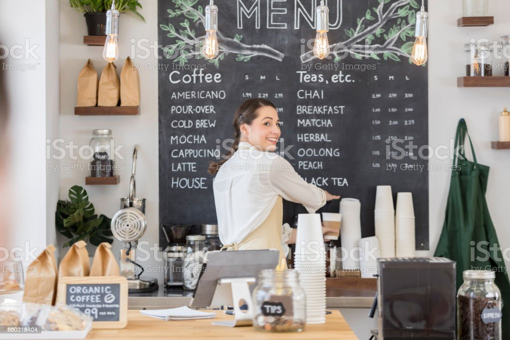 Female barista looks over her shoulder stock photo