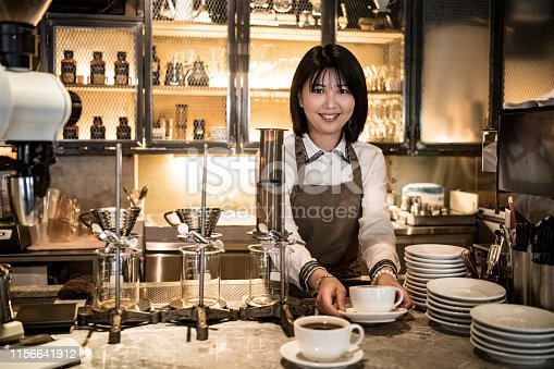 Cheerful mid adult woman with bobbed hair with fresh coffee, smiling at camera, service, food and drink