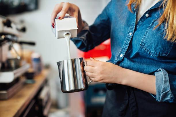 weibliche barista gießen milch in der kanne im café - stoffe berlin stock-fotos und bilder