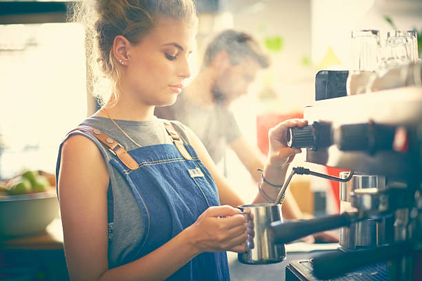 female barista steaming milk in cafe - barista making coffee stock pictures, royalty-free photos & images