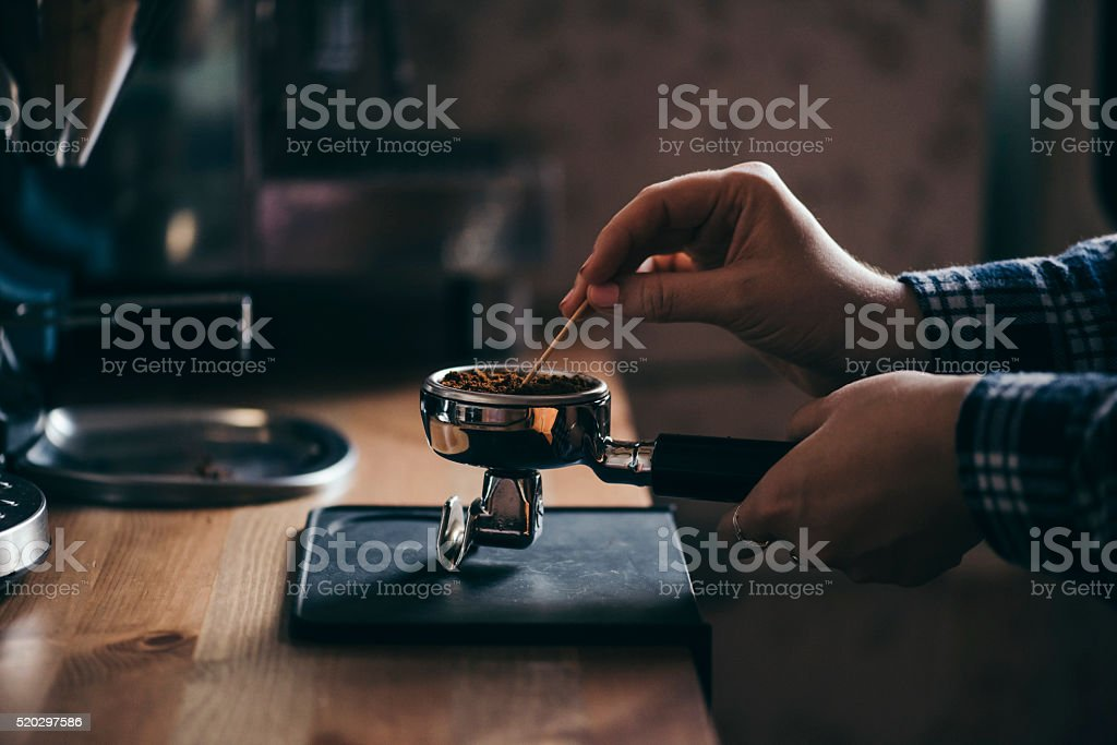 Female barista tamping coffee in a portafilter stock photo