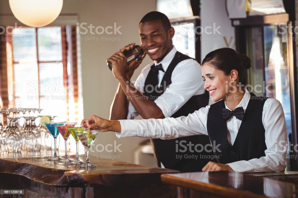 Female bartender garnishing cocktail with olive stock photo