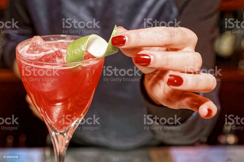 Female bartender is adding citrus zest to cocktail, toned stock photo