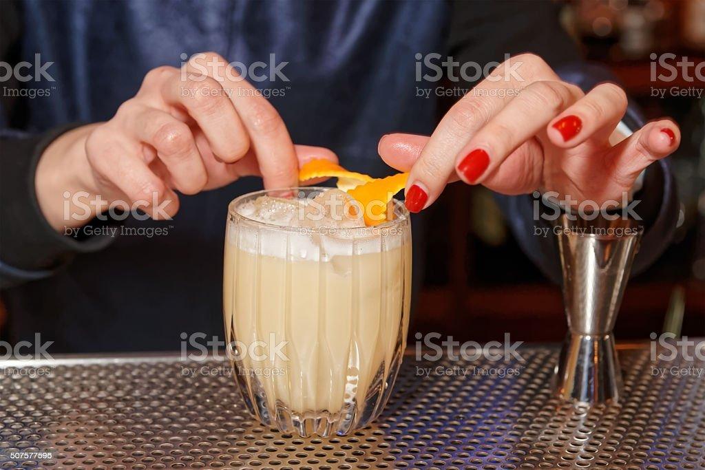 Female bartender is adding orange zest to cocktail stock photo