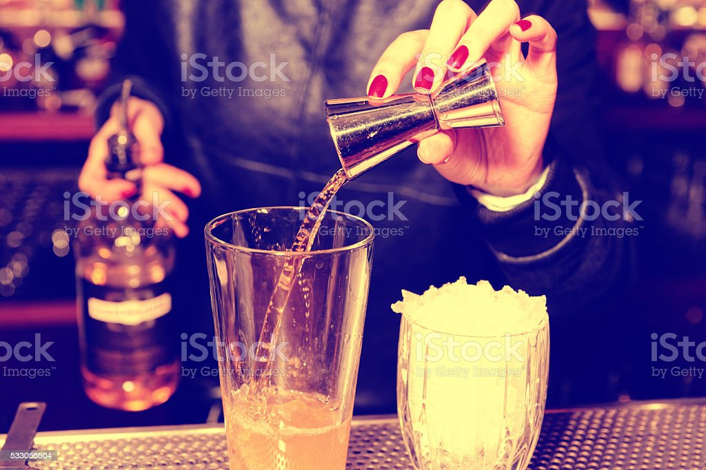 Female bartender is adding whisky to the glass, toned image stock photo