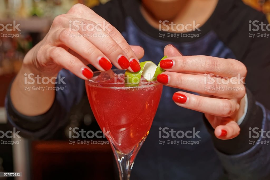 Female bartender is decorating a cocktail stock photo