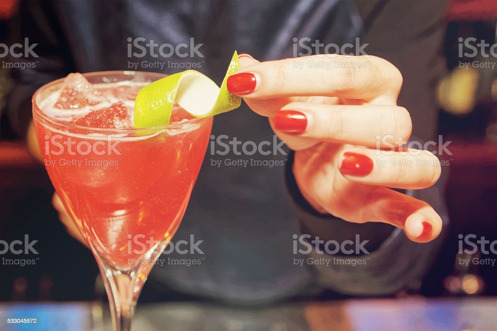 Female bartender is decorating a cocktail, toned stock photo