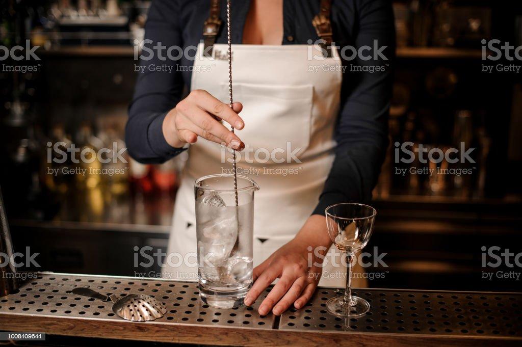 Barman feminino um gelo no copo de mistura - foto de acervo