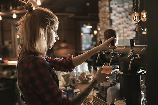 female bartender pouring beer from tap at bar - beer pour stock photos and pictures