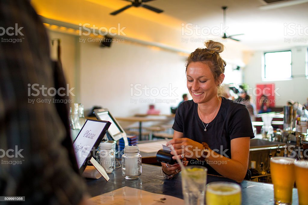 Female bartender taking electronic payment transfer behind bar stock photo