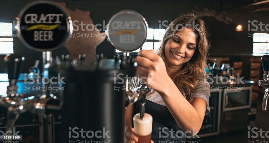 Female bartender tapping craft beer in bar stock photo