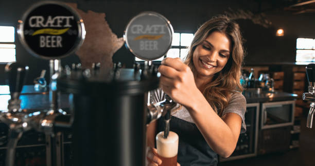 female bartender tapping craft beer in bar - bartender стоковые фото и изображения