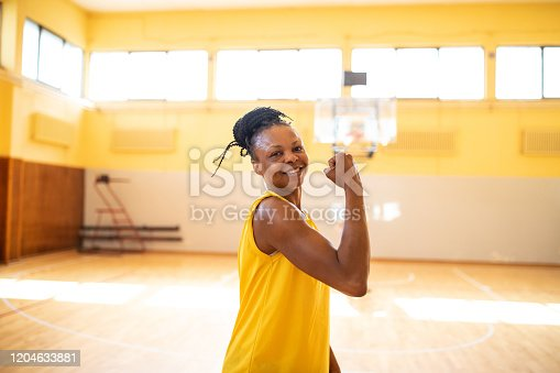 Portrait of African female basketball player standing on basketball court, flexing biceps and looking at camera