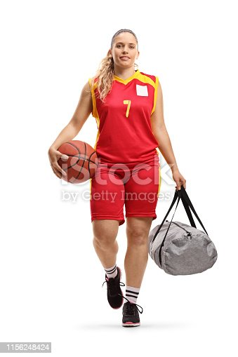 istock Female basketball player in a jersey walking and carrying a ball and a sports bag 1156248424