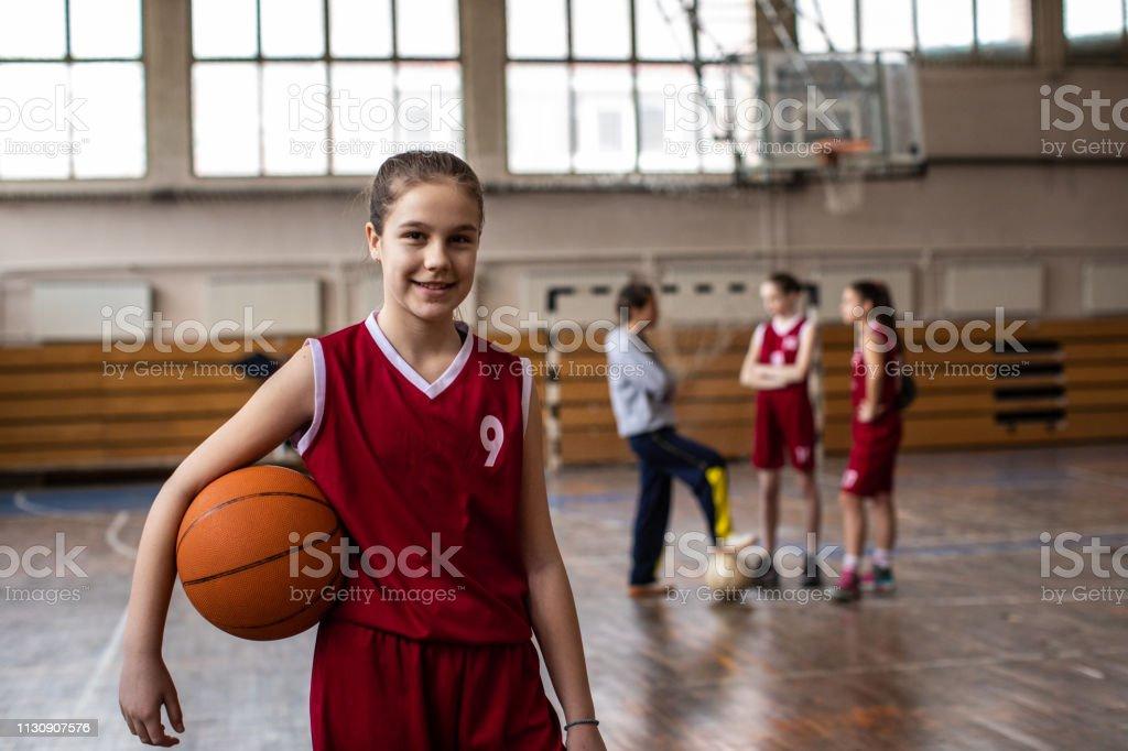 Teenage girls wearing basketball uniform and holding ball, looking at...