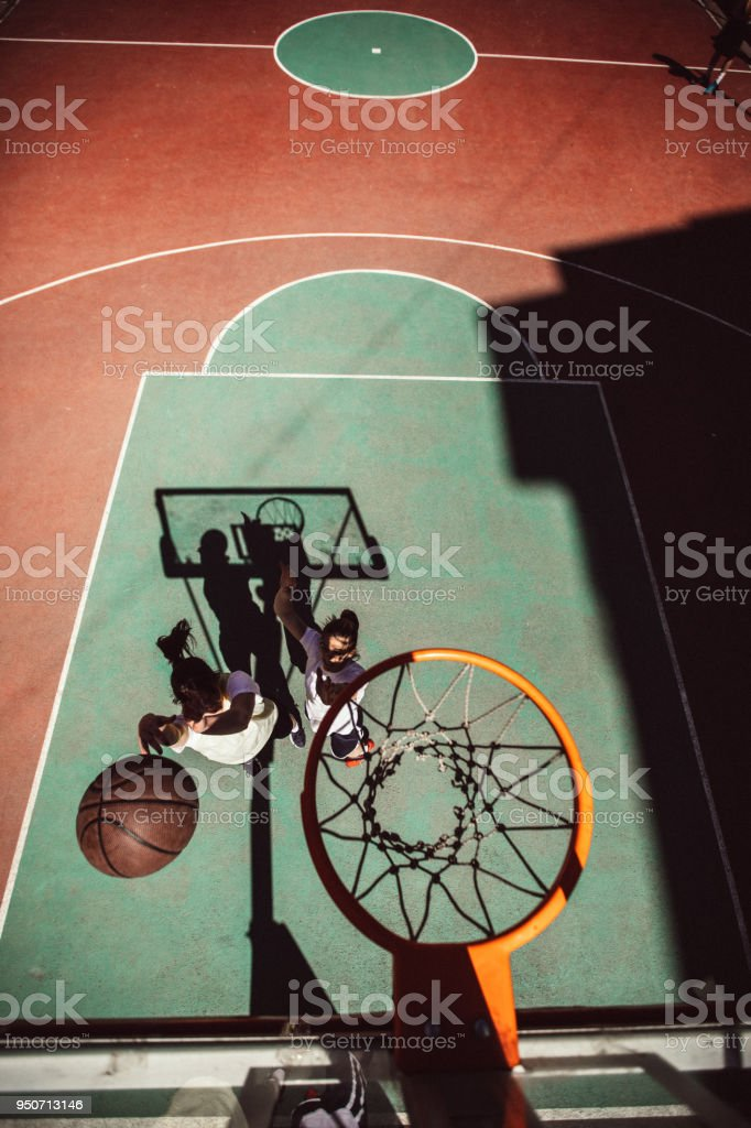 Two young women on the street playing basketball, high angle view