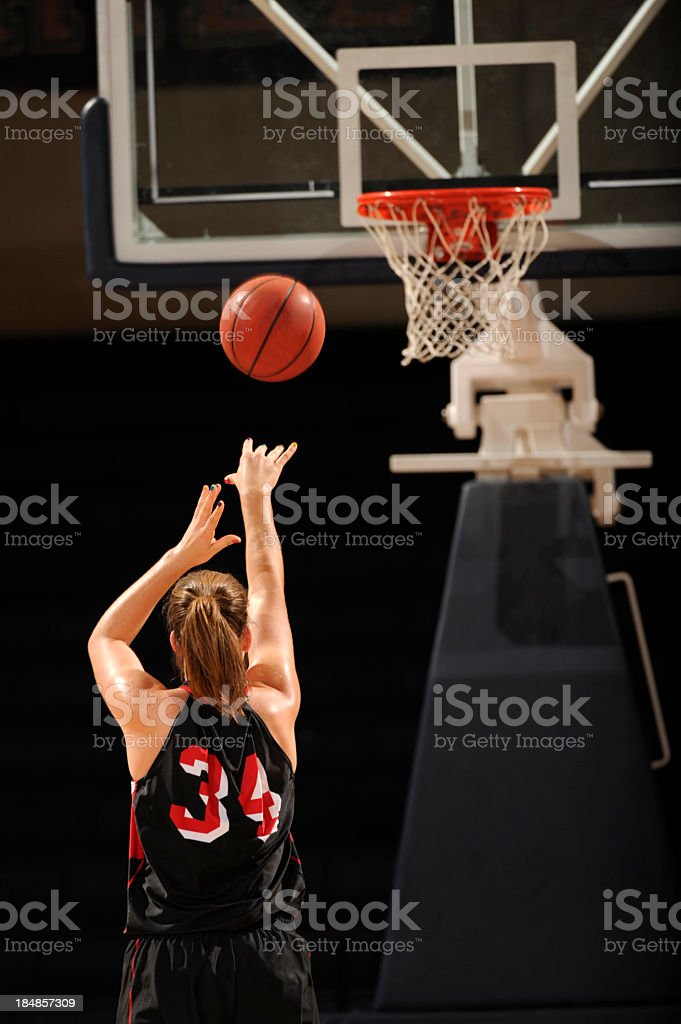 Female basketball player throwing a free throw toward basket stock photo