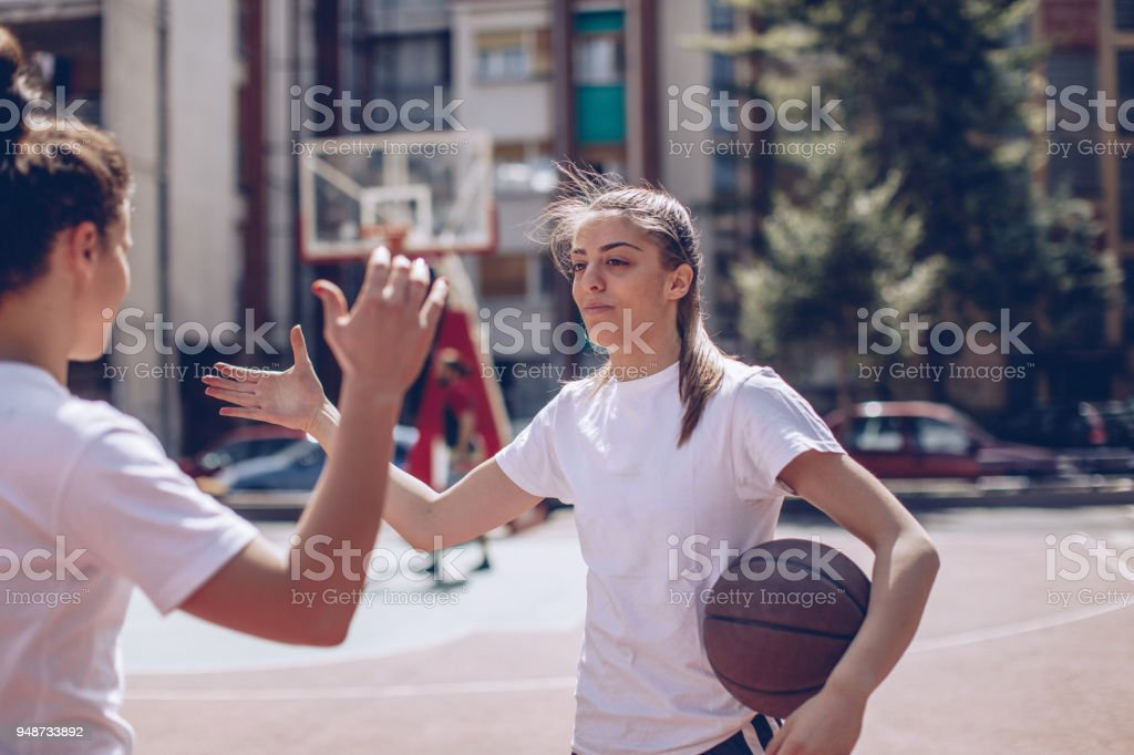 Female basketball players greeting stock photo