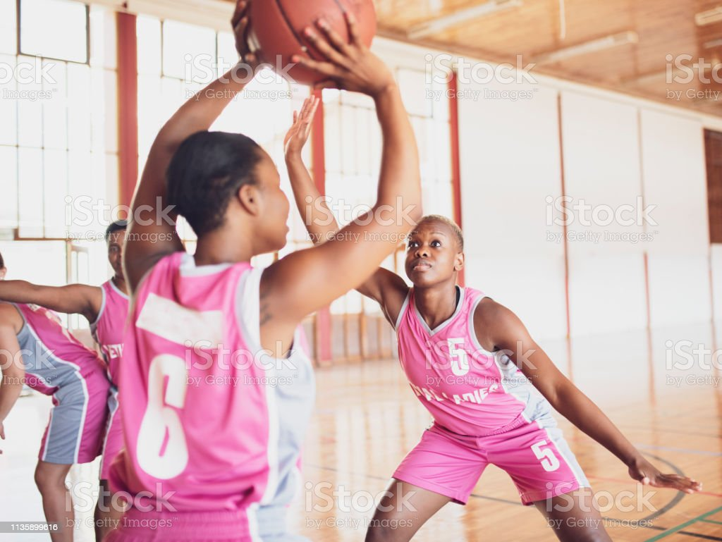 Female basketball player defending ball from opposing team at gym....