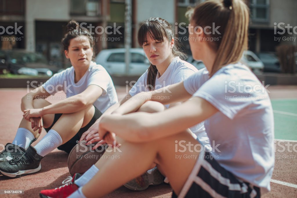 Female basketball players sitting on the court stock photo