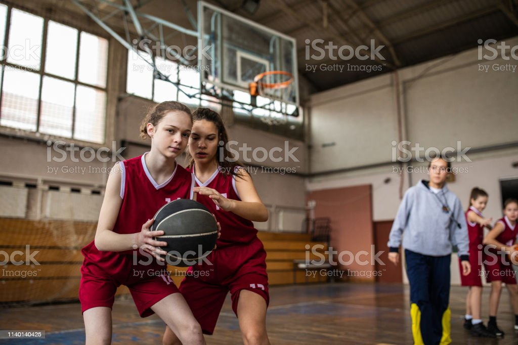 Teenage girls playing basketball, young female coach standing and...