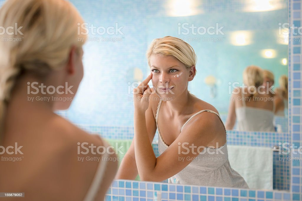 Female beauty applying lotion at home stock photo