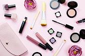 パステル調の背景に女性の美しさのアイテム。ピンクの財布に、製品、花を作る。