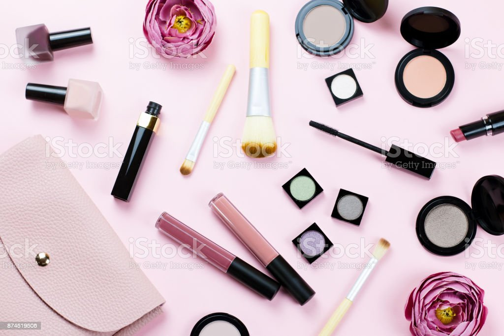 Female beauty items on pastel background. Pink purse, make up products, flowers. stock photo