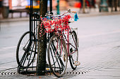 Female Bicycle Equipped Basket With Decorative Flowers Parked In City Street