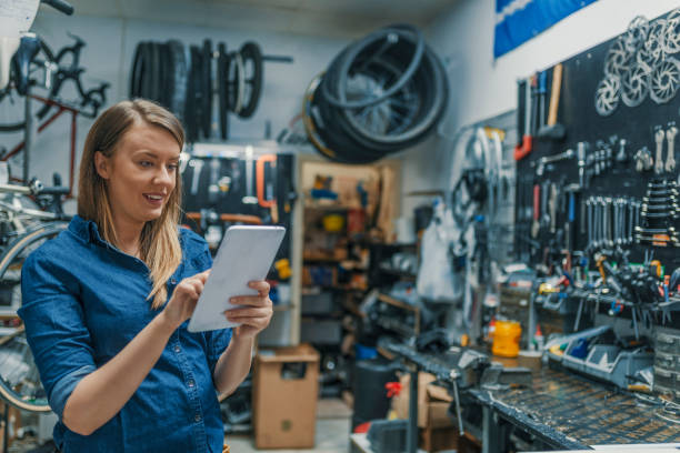 Female bicycle repair technician using digital tablet in bicycle shop Female mechanic at work. Using a tablet while fixing a bicycle. Female bicycle repair technician using digital tablet in bicycle shop. Verify the checklist. Mechanic woman checking something on a tablet-pc and checklist. bicycle shop stock pictures, royalty-free photos & images