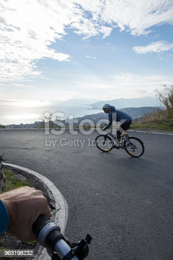 View past handlebars and road to distant view, Liguria