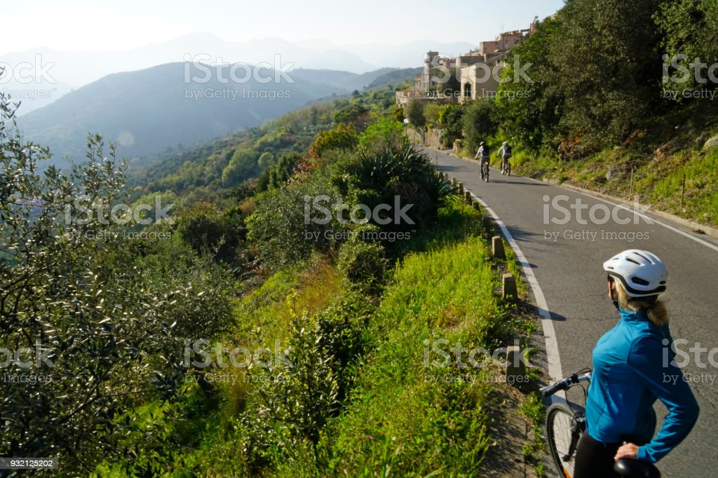 Female bicyclist on rural road, enjoying the view stock photo