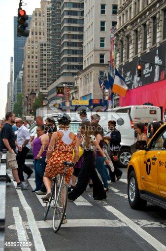 583973114istockphoto Female Bicyclist & pedestrians at 34th St, Manhattan, NYC 458927859