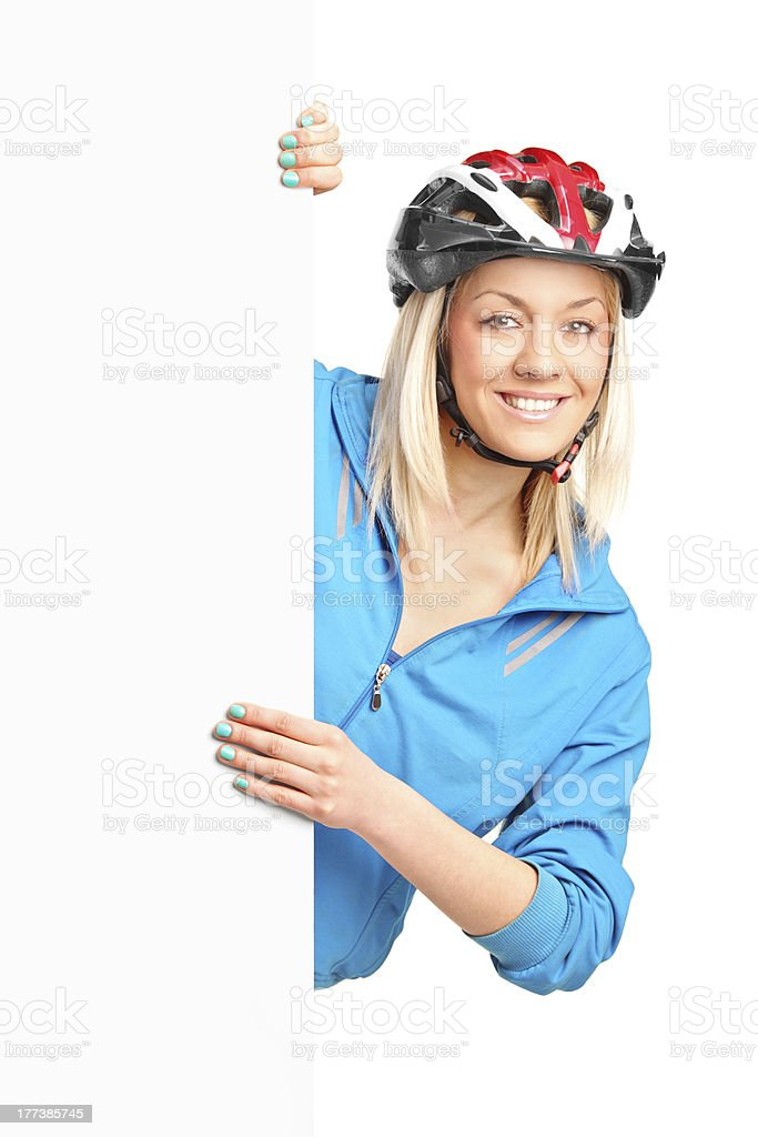 Female bicyclist posing behind a white panel stock photo