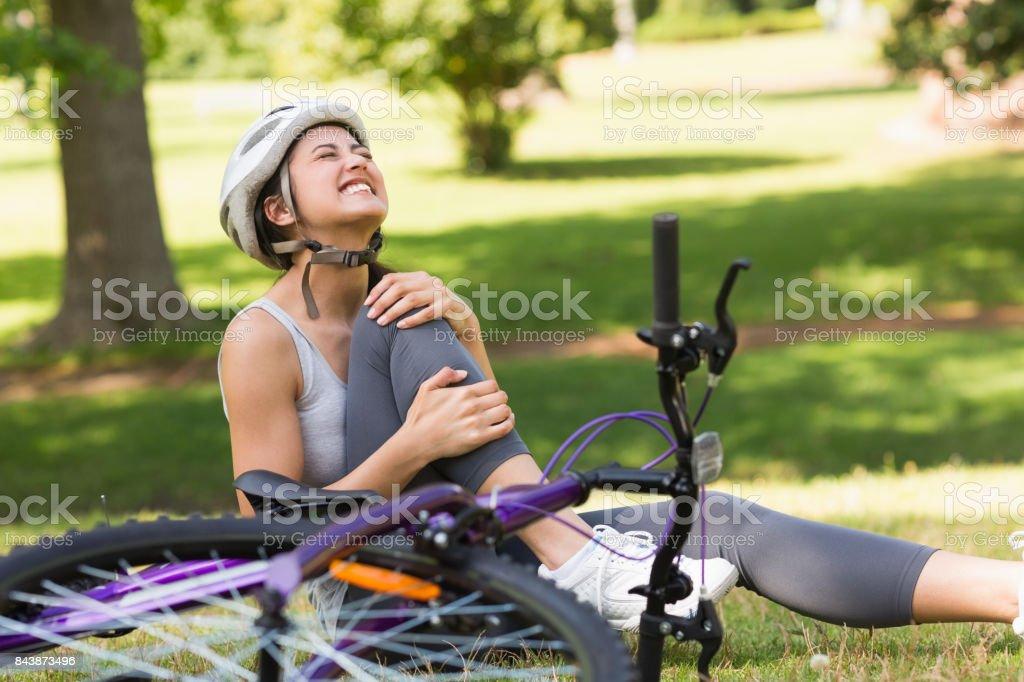 Cycliste femme avec jambe mal assis dans le parc - Photo