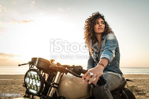 Beautiful female biker driving a cafe' racer motorbike - Pretty girl driving a motorbike and enjoying the roadtrip