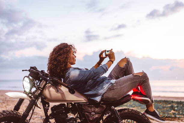 Female biker driving a cafe' racer motorbike Beautiful female biker driving a cafe' racer motorbike - Pretty girl driving a motorbike and enjoying the roadtrip female biker resting stock pictures, royalty-free photos & images