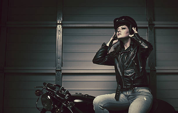 female biker taking off helmet stock photo
