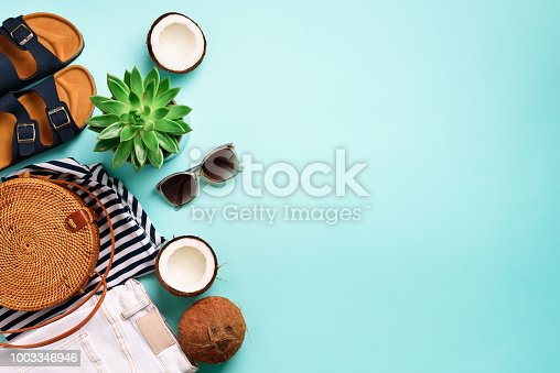 istock Female birkenstock sandals, jeans, striped t-shirt, rattan bag, coconut and sunglasses on blue background with copy space. Top view. Summer fashion, capsule wardrobe concept. Creative flat lay 1003346946