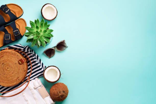 sandali birkenstock femminili, jeans, t-shirt a righe, borsa in rattan, cocco e occhiali da sole su sfondo blu con spazio di copia. vista dall'alto. moda estiva, concetto di guardaroba a capsule. lay piatto creativo - flat lay foto e immagini stock