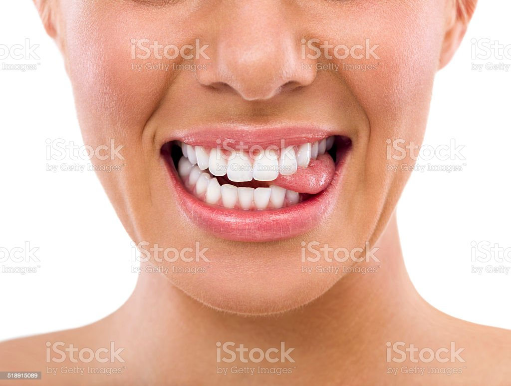 Female biting tongue with perfect teeth stock photo