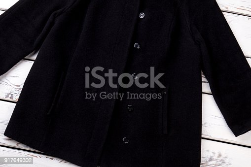 Female black buttoned coat. New collection of female outwear, wooden background. Female elegance and style.