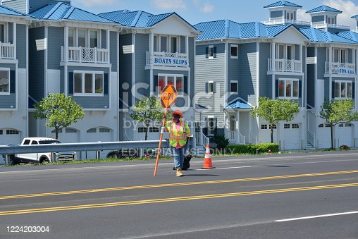 A mature lone black female flagman looks into oncoming traffic as she rests on the sign staff in front of luxury condos on a bright spring day as the road is repaired in Ocean City, Maryland in preparation for lifting of the Governors Stay at Home order during the covid-19 pandemic