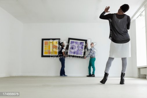 Female black Gallery owner hanging a picture in an art gallery. Horizontal shot.