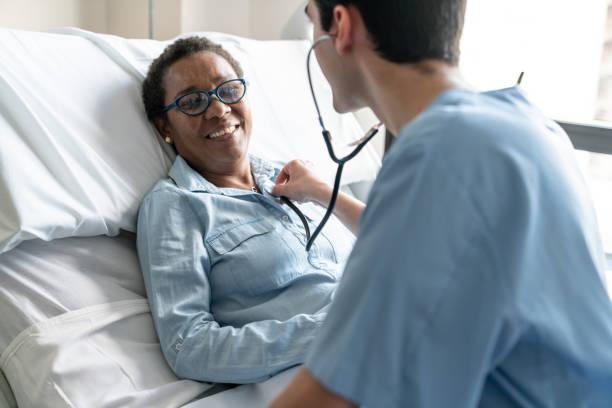 간호사는 그녀의 마음을 확인 하는 동안 병원 침대에 누워 여자 흑인 환자 이길 청진 기 - 환자 뉴스 사진 이미지