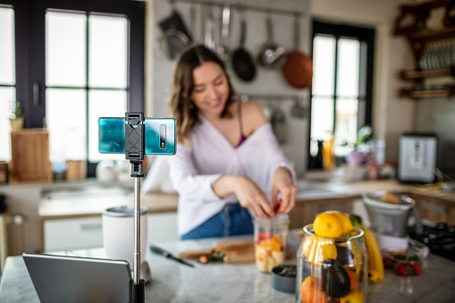 Photo of young woman in kitchen live streaming about healthy food.
