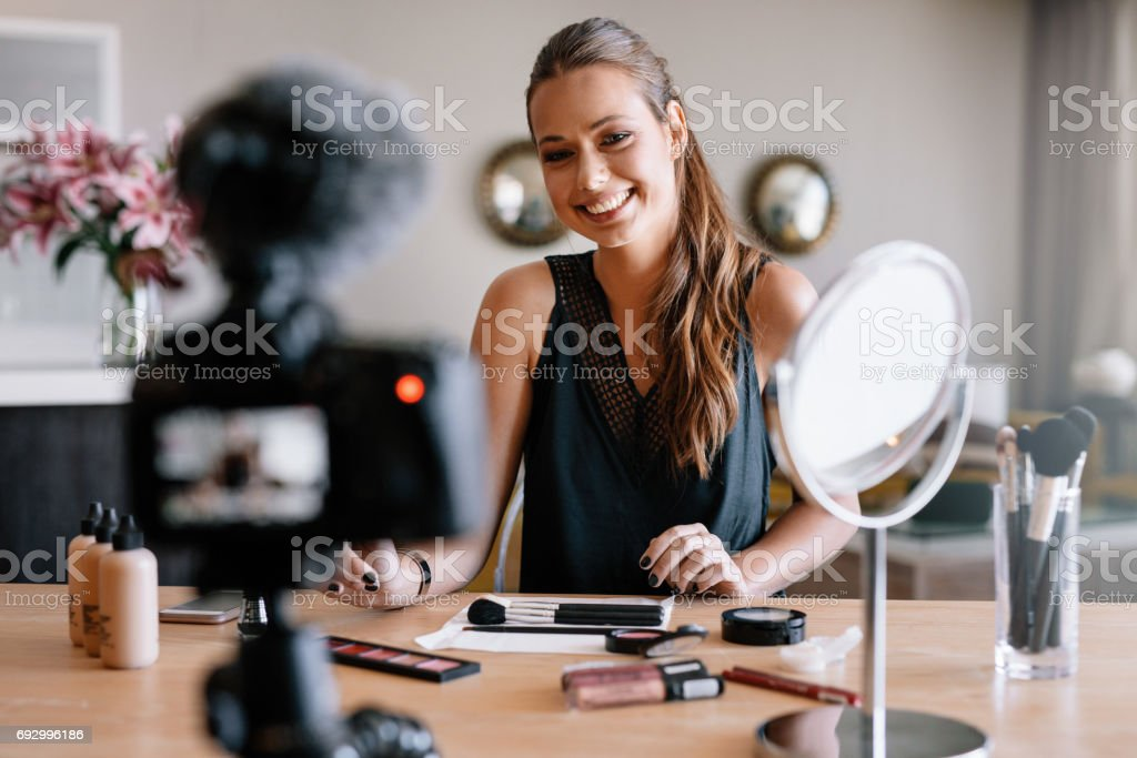 Female blogger recording video for her vlog on beauty and fashion theme. stock photo