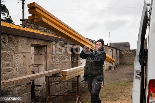A young female construction worker carries planks of wood as she works outdoors.