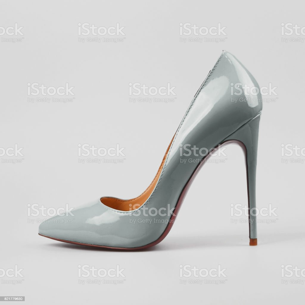 female blue high-heeled shoes over grey stock photo