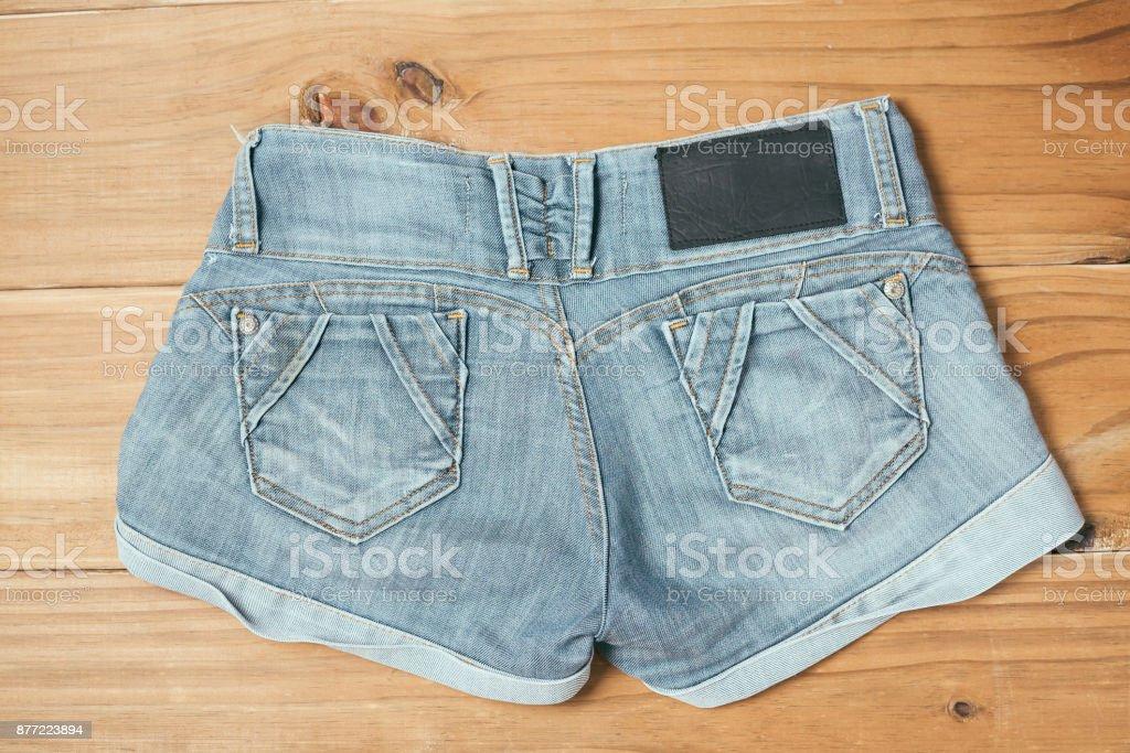 70c5cf4833 Pantalones cortos de mujer jeans rotos azul sobre fondo de madera vieja  foto de stock libre